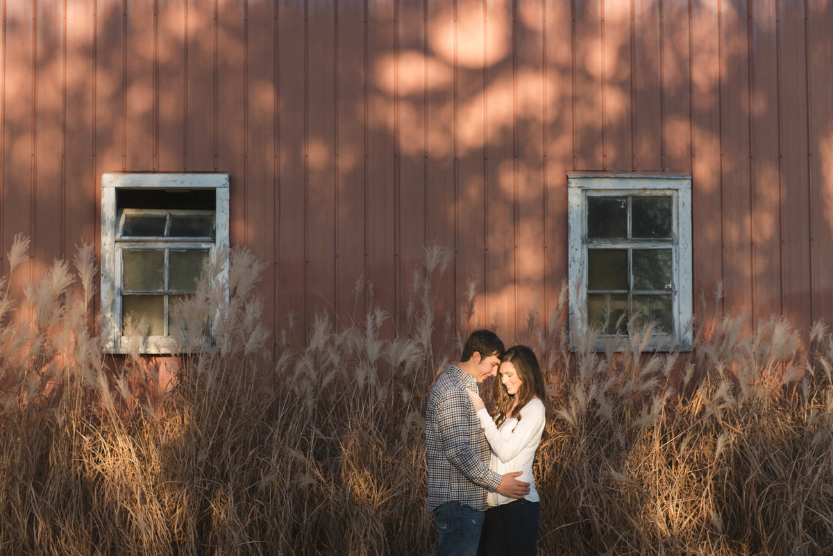 Engaged couple cuddling in pool of light against old red barn
