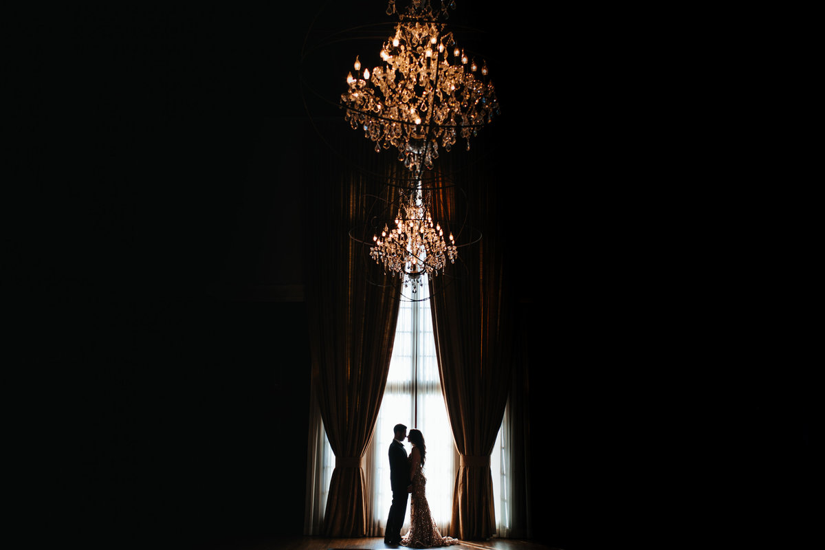 A dramatic photo of a couple against a giant window with large chandeliers over them