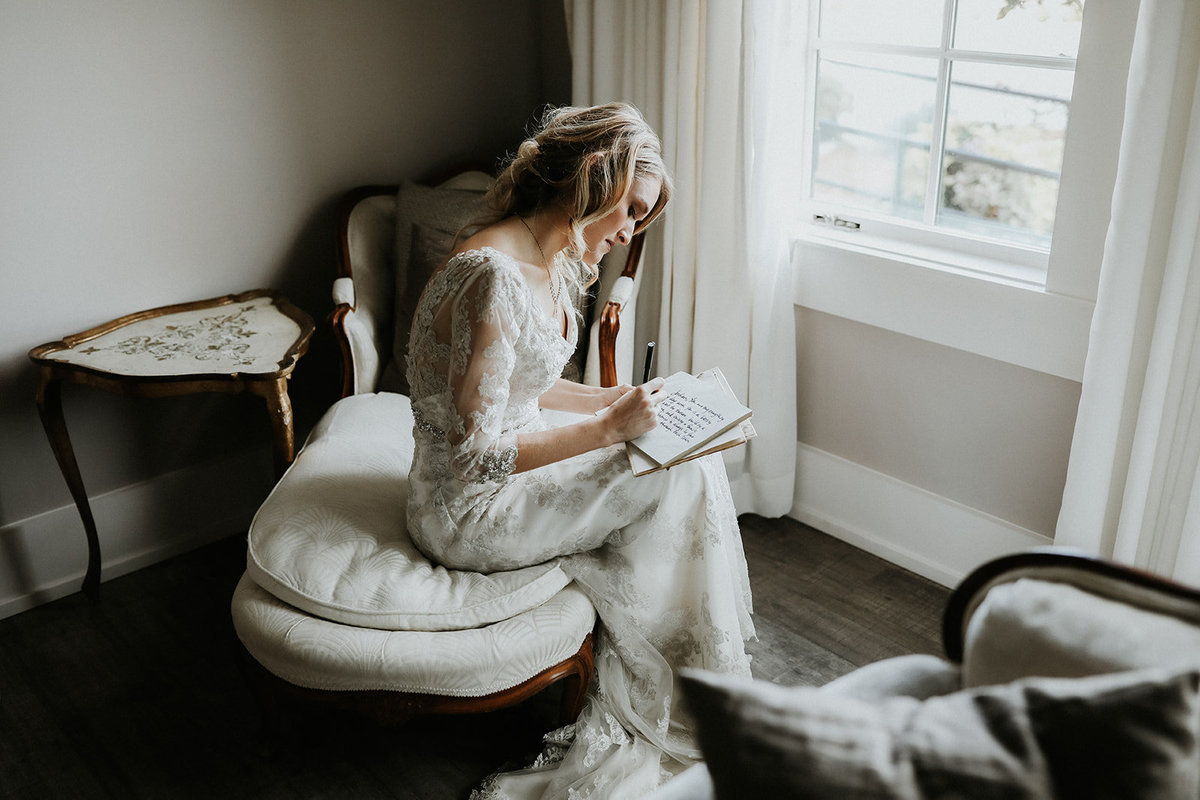 A bride sits and writes her wedding vows.