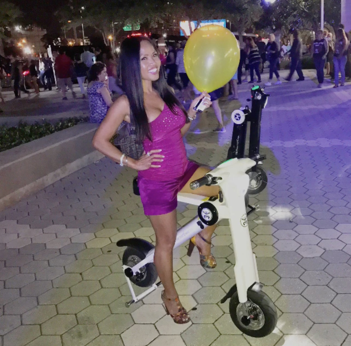 Lady with ballon having night out on the town on White Go-Bike M1