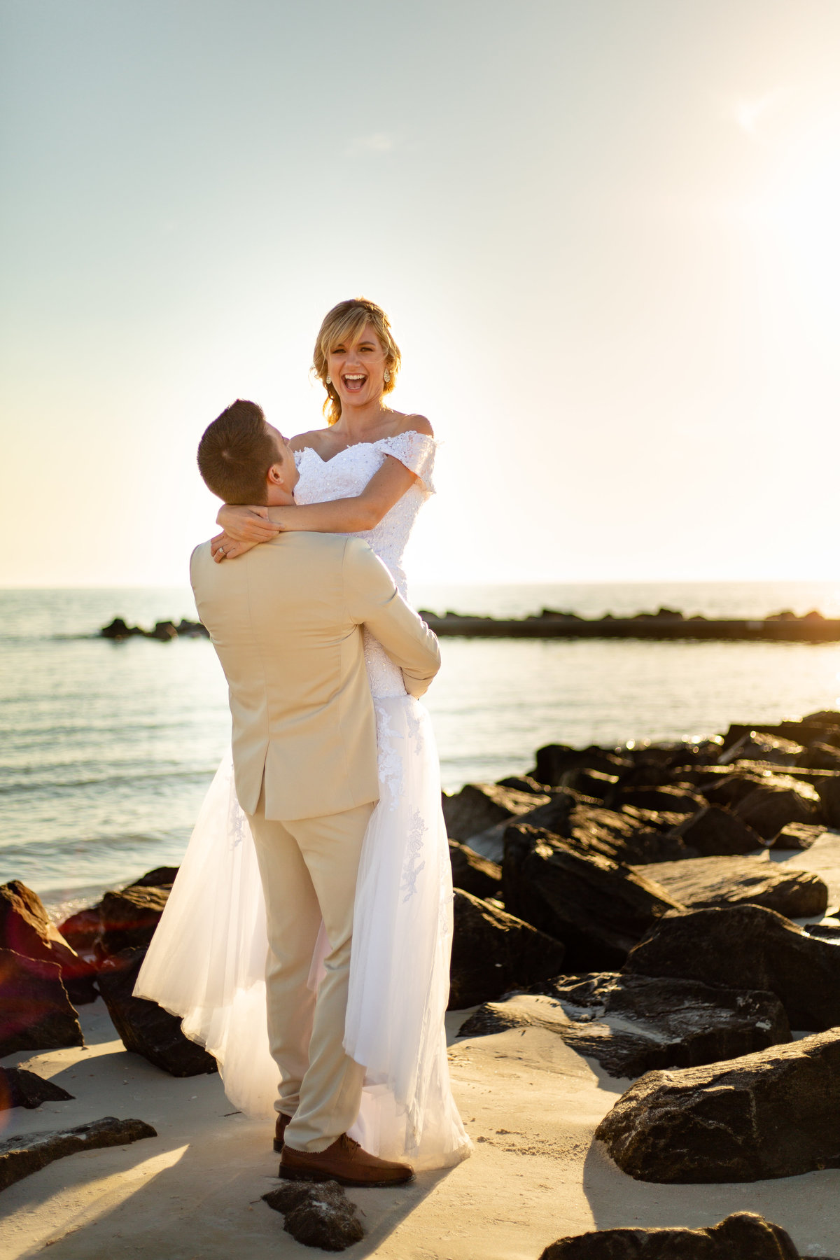 Bride joyfully smiles at camera on Dunedin, Florida during sunset with golden hour glow as her groom in his tan suit lifts her up and spins her romanctically