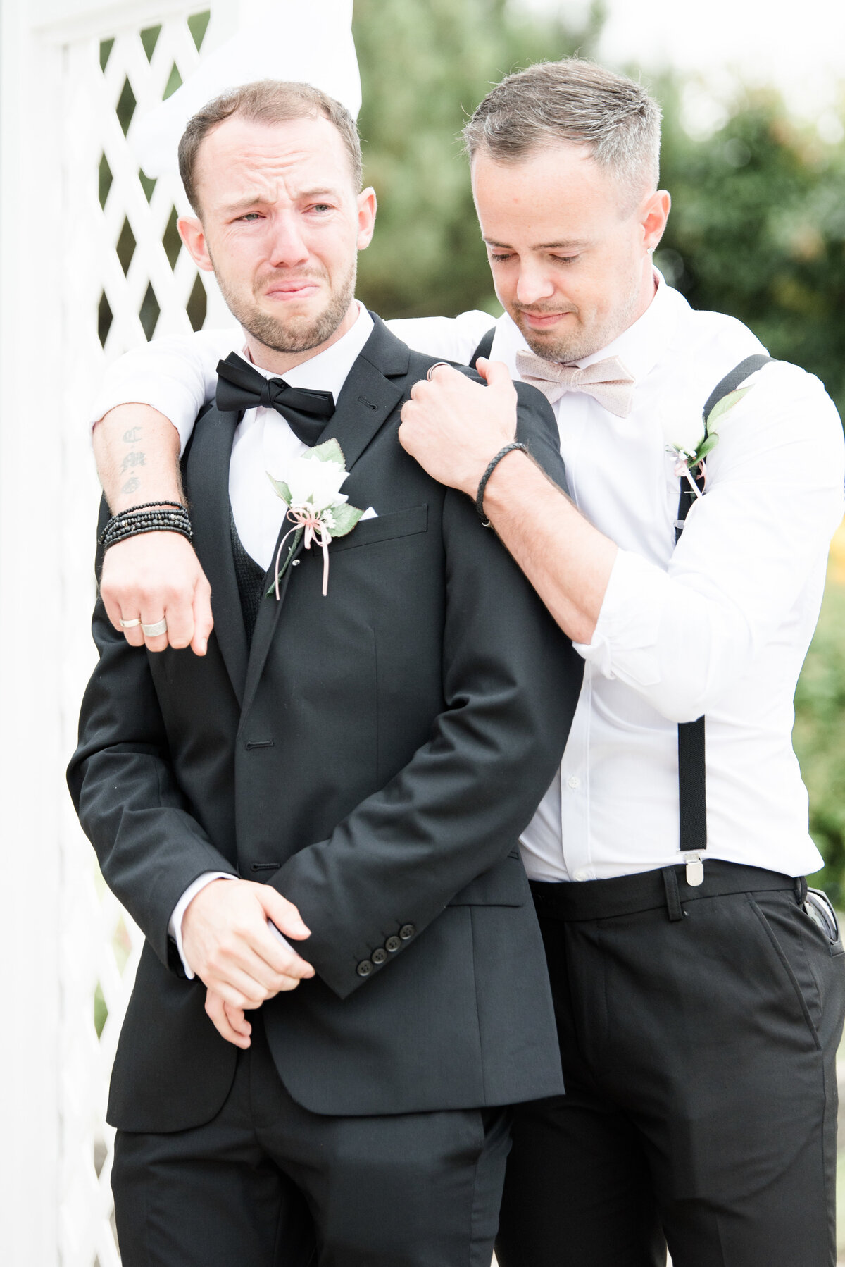 A groom tears up as he watches his bride down the aisle is comforted by his best man