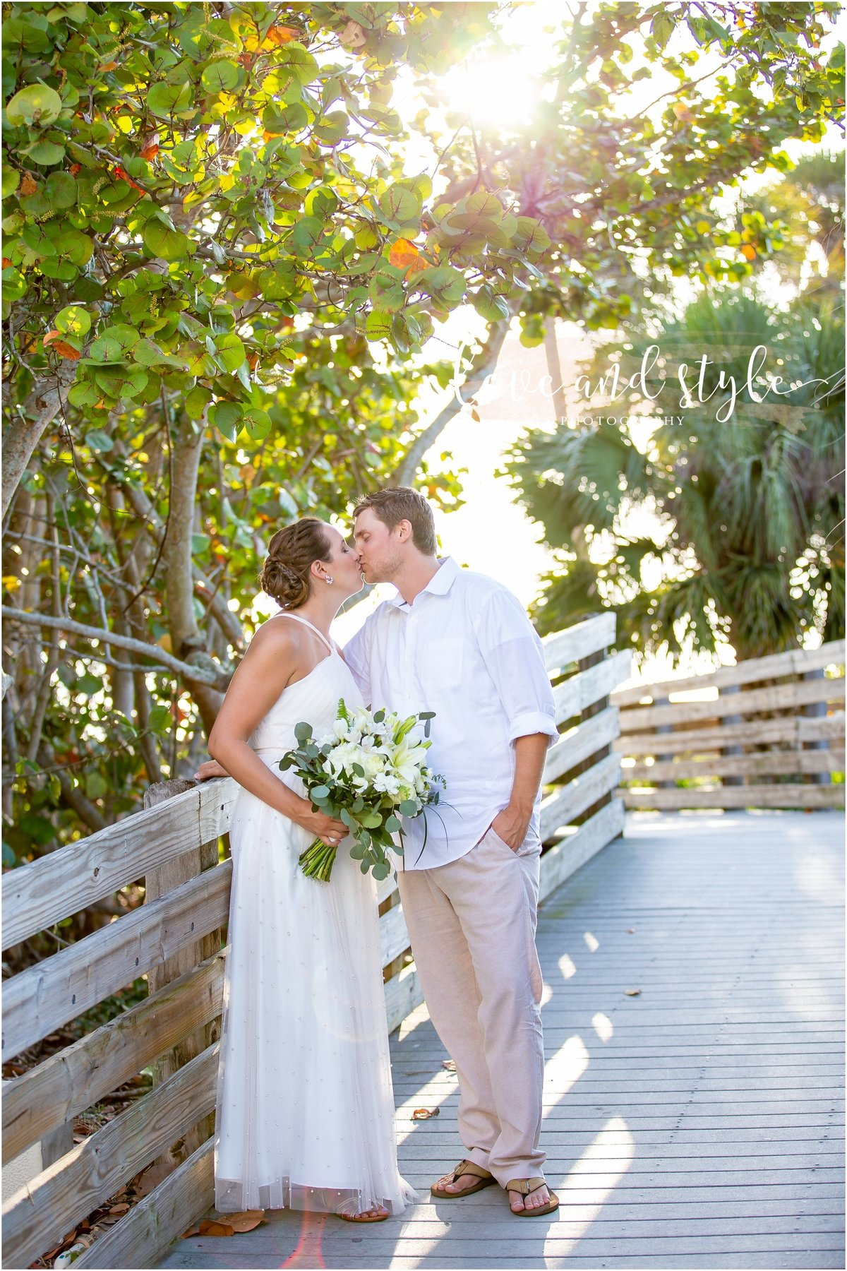 Lido Beach Wedding Photography of bride and groom kissing on the wooden pathway to the beach