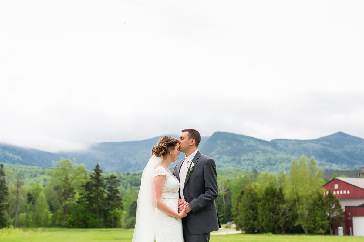 The couple share a moment in front of the mist covered White Mountains after their wedding at Waterville Valley Resort in New Hampshire