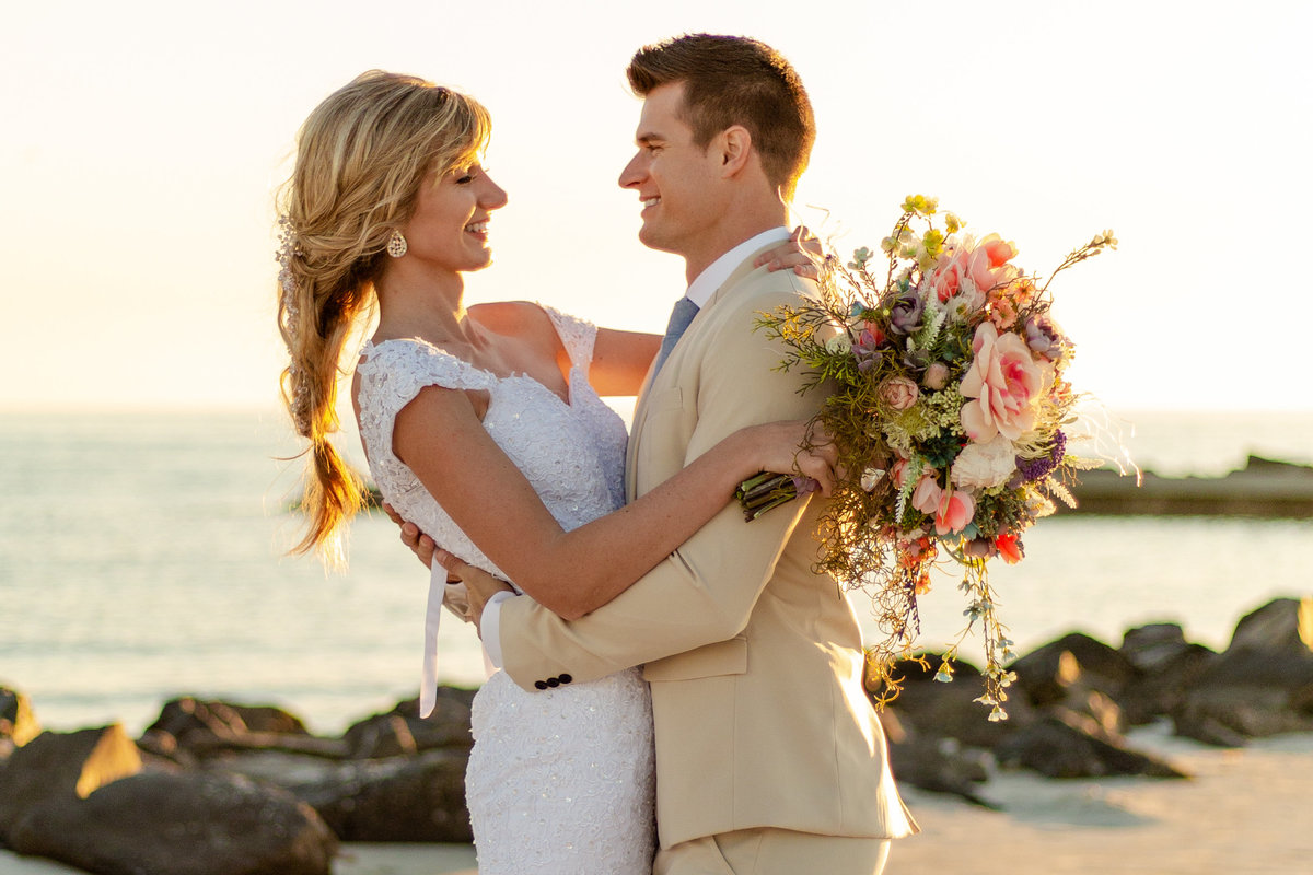 Bride and groom smile at each other on the beach in Dunedin, Florida at sunset with her colorful bridal bouquet with her hair in a mermaid hairstyle braid