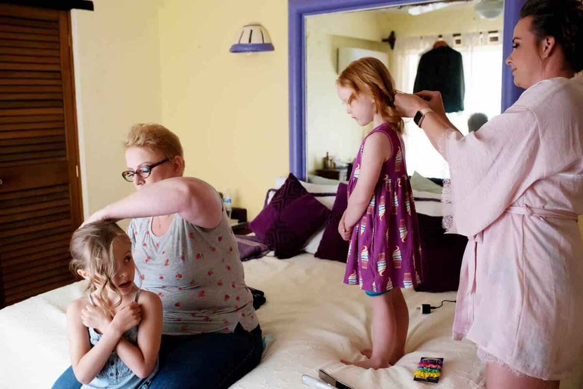 two women curl the hair of 2 little girls before a wedding