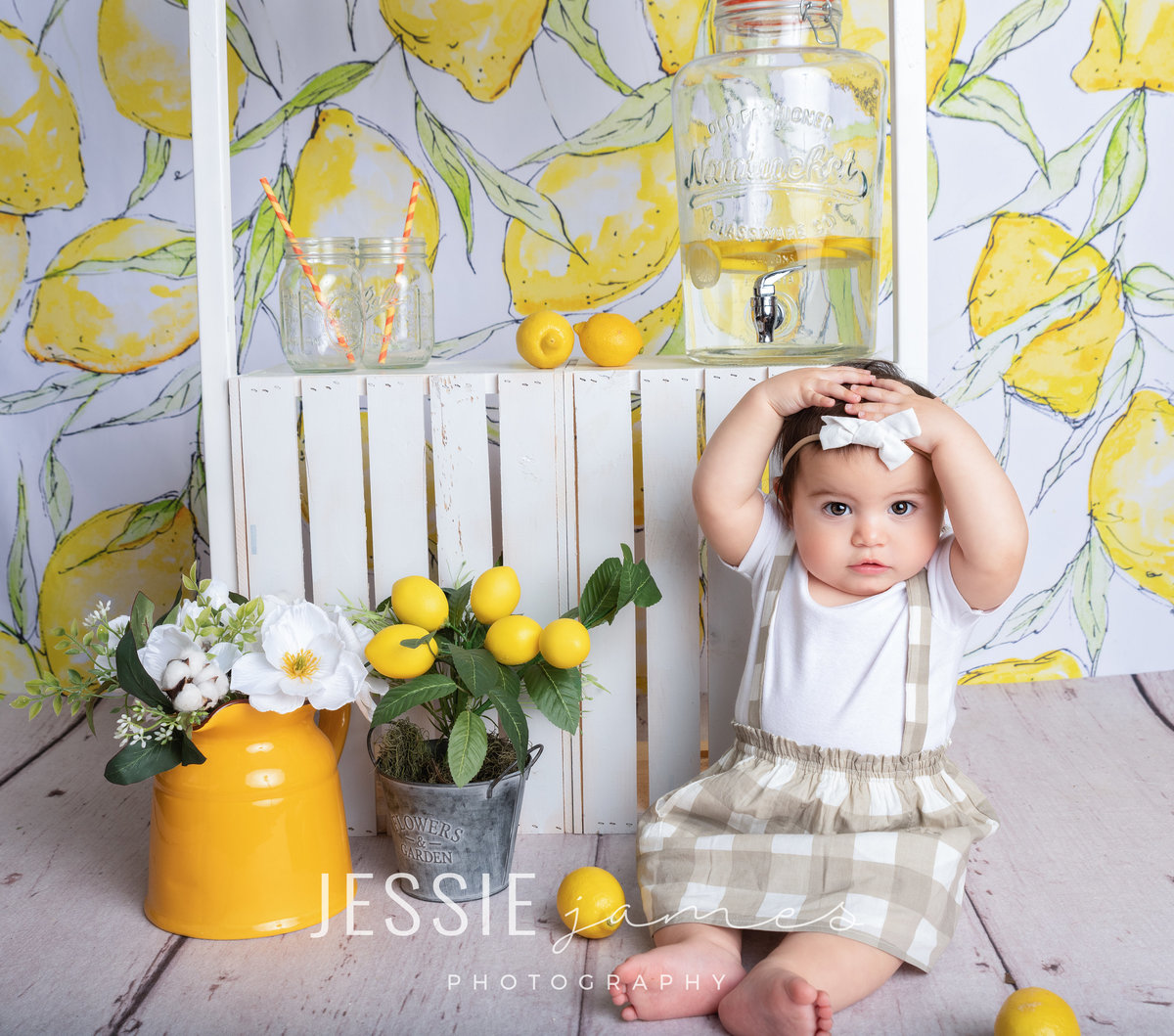 baby girl sitting in front of a lemonade stand for a lemonade themed photoshoot