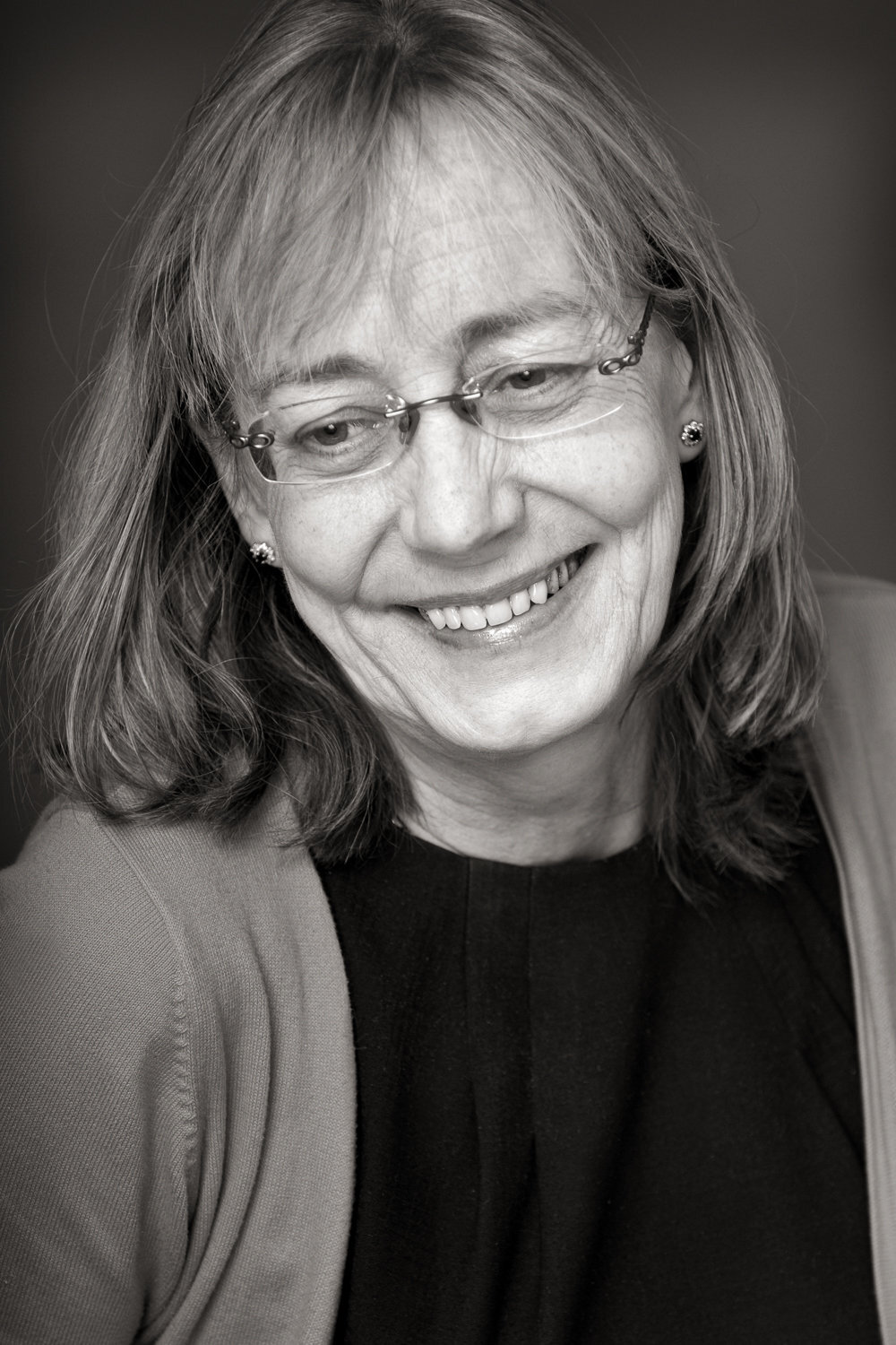Black & white portrait of an  female  doctor wearing glasses and smiling