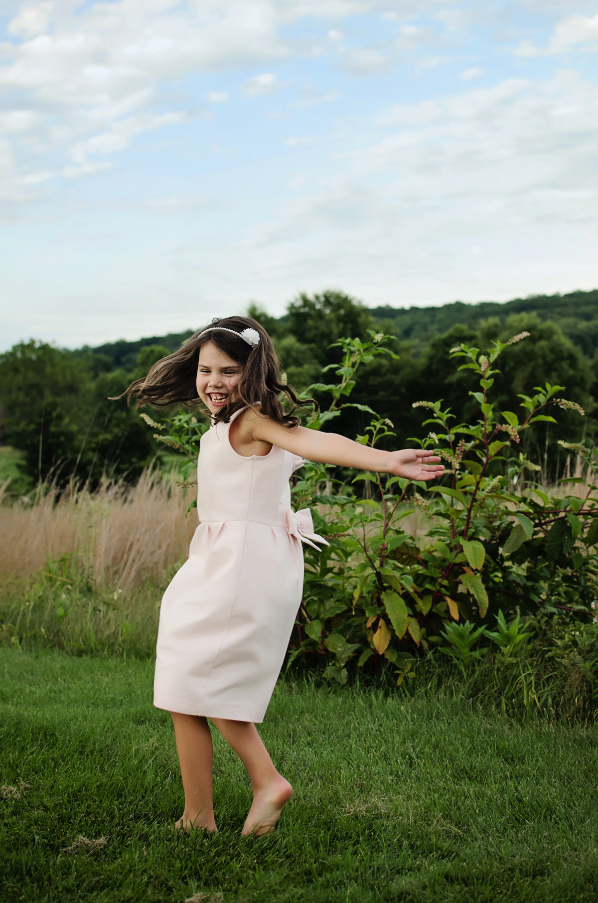 Portrait of a happy little girl twirling with puffy clouds in Northern Virginia taken by Sarah Alice Photography