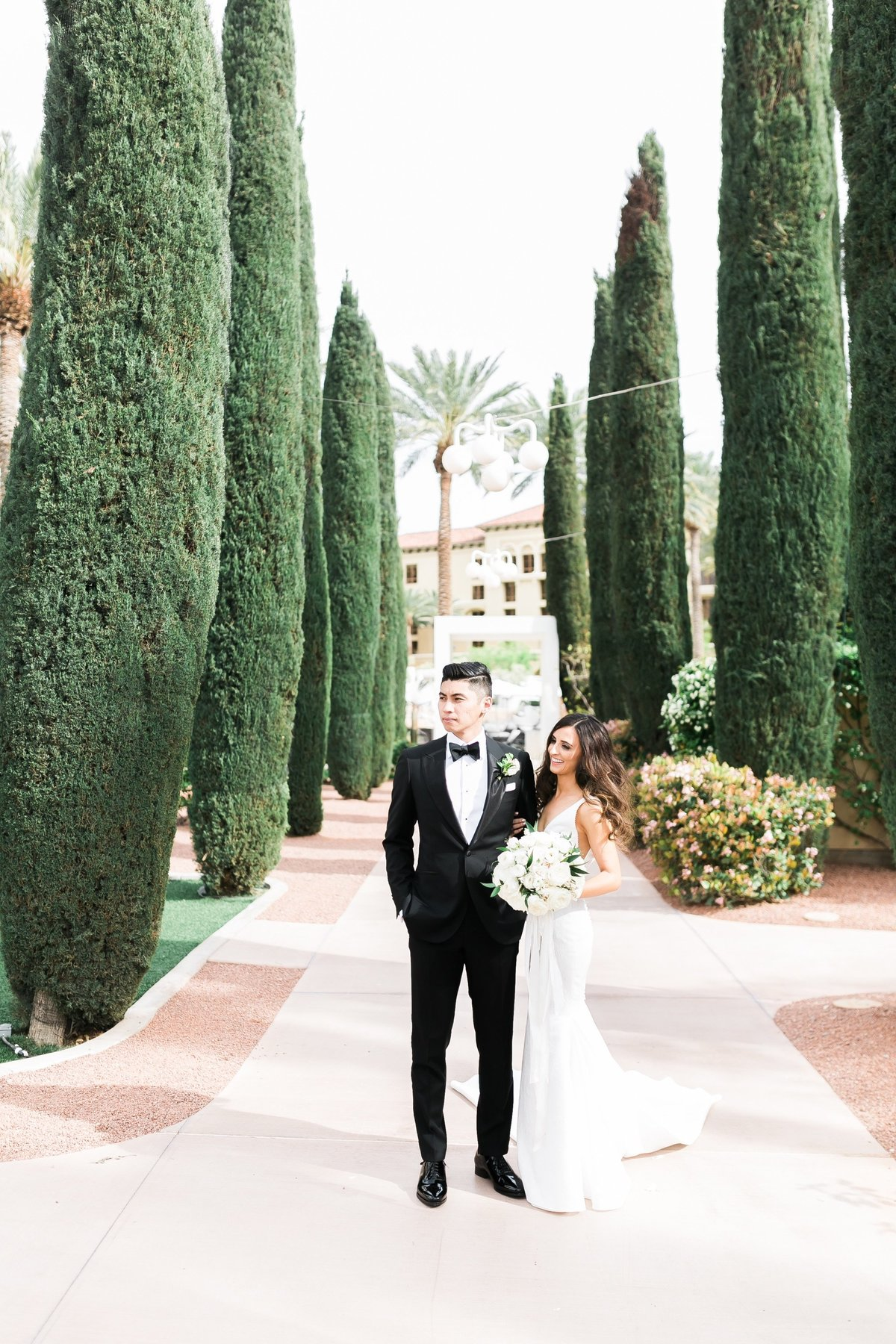 a photo of a bride and groom on a walkway that is lined by large topiaries trees at a wedding at Green Valley Ranch in Las Vegas