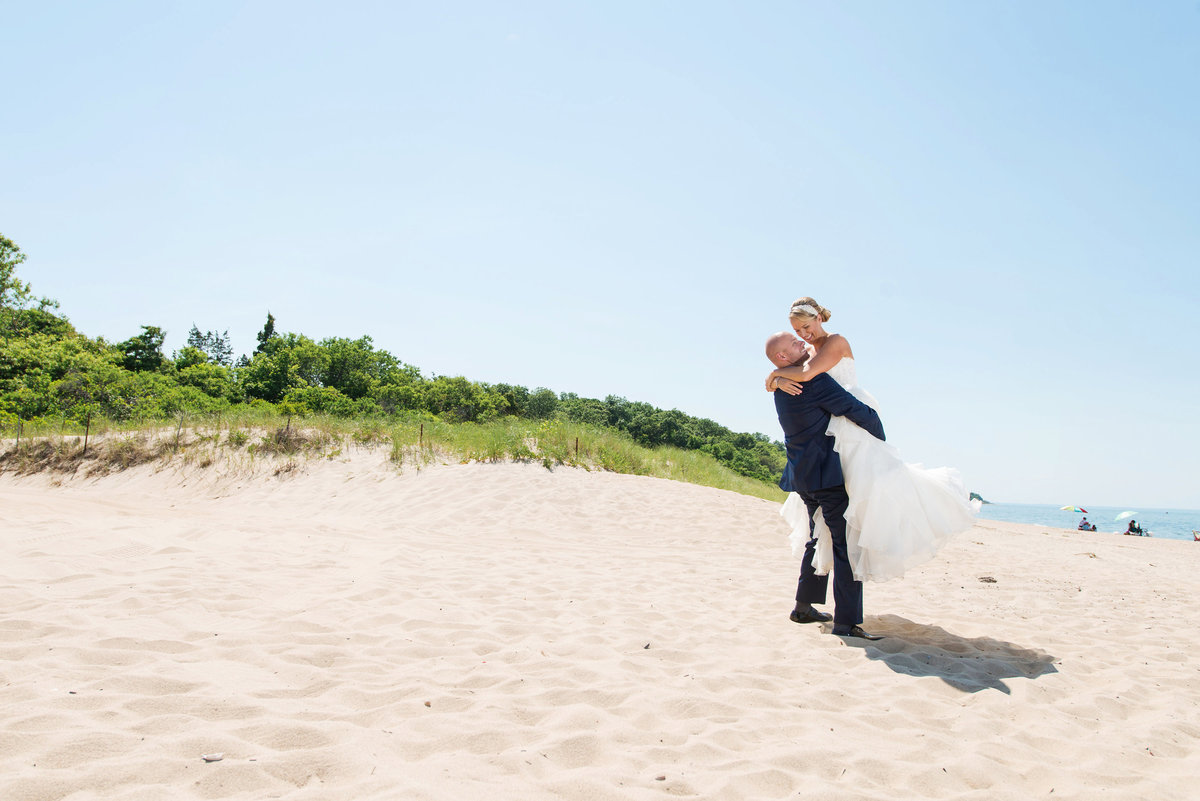 photo of groom holding his bride in the air on the beach from wedding reception at Pavilion at Sunken Meadow