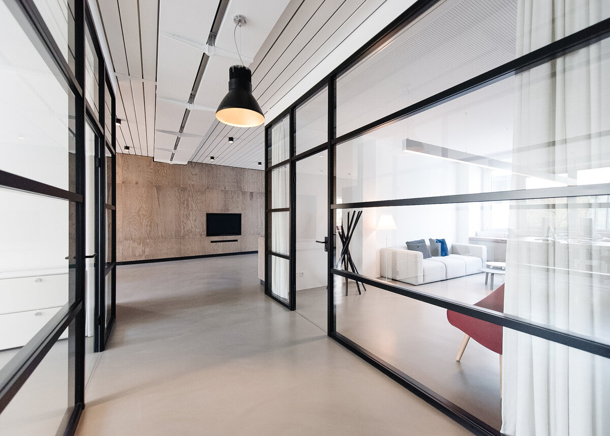 A smart office has black crittal doors with a black pendant and poured concrete floors.