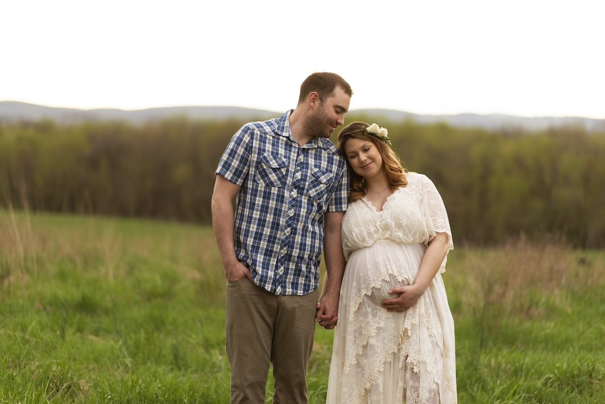 ivory lacy  maternity gown pregnant coupon with mountains in backgroound