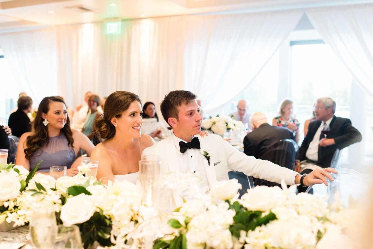 Bride and groom enjoying their elegant white wedding reception.