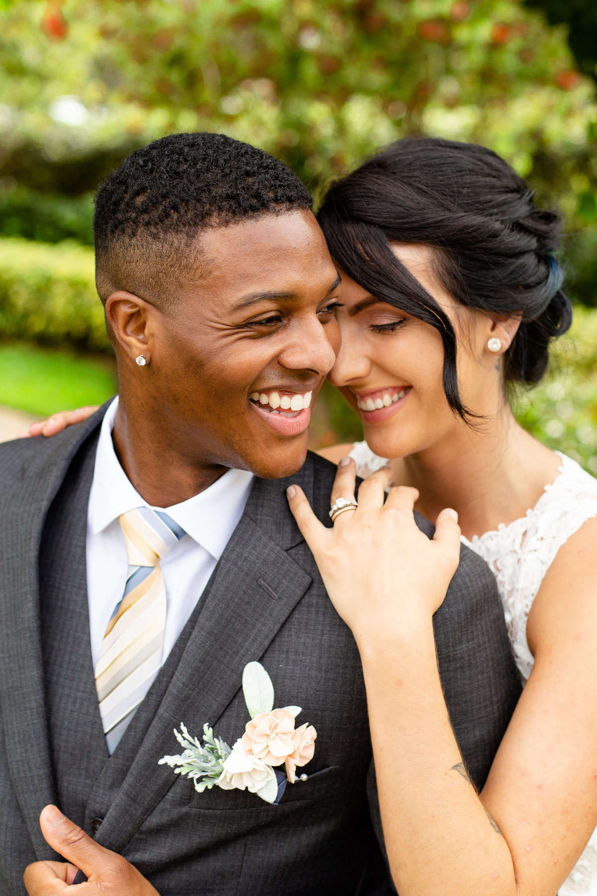 Bride and groom smile at each other on their wedding day in Orlando, Florida with groom in grey suit and boutonniere
