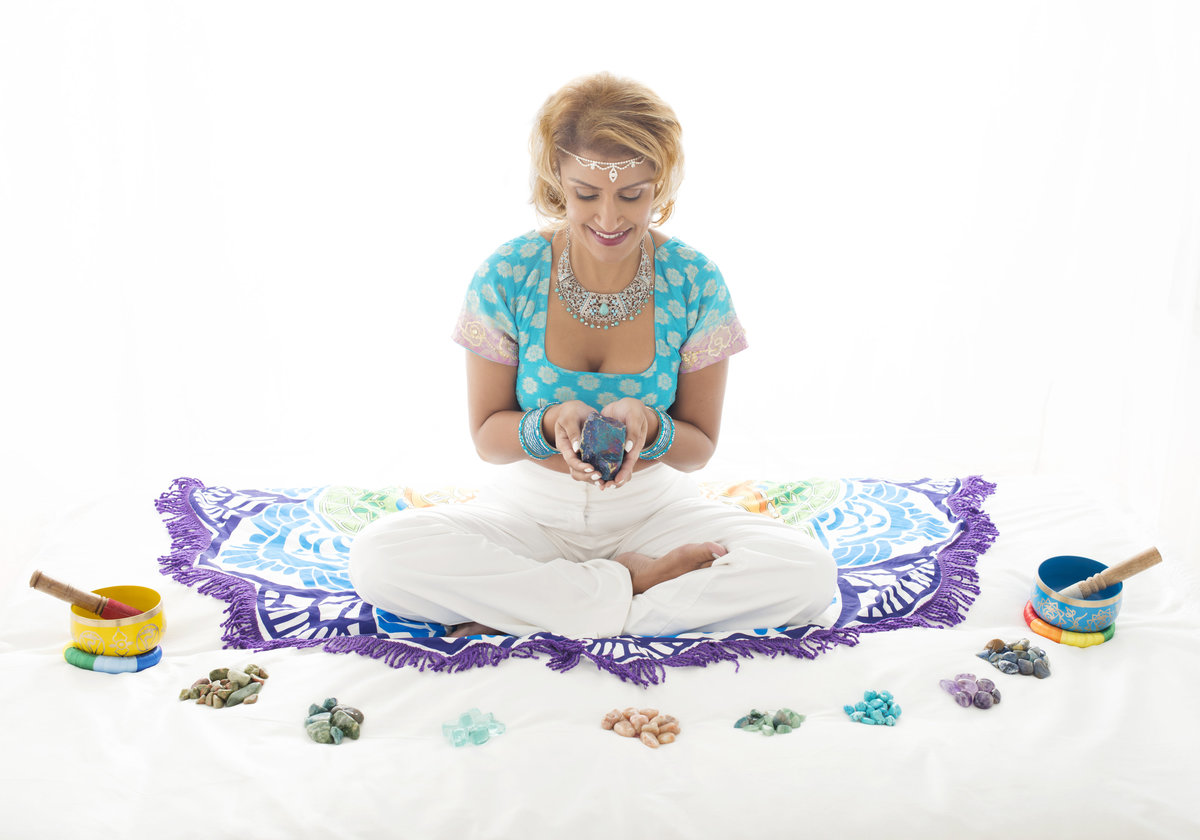 meditation coach personal branding photo  sitting on the ground with folded hands  praying  in aqua  color top