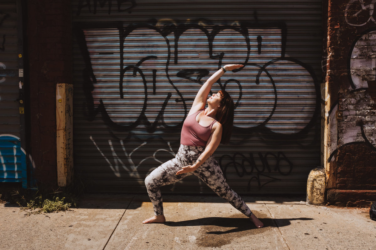 yoga teacher in reverse warrior against graffiti door