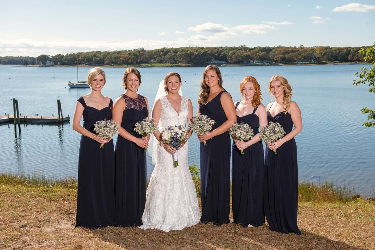 Bride and bridesmaids by the water at The Ram's Head Inn