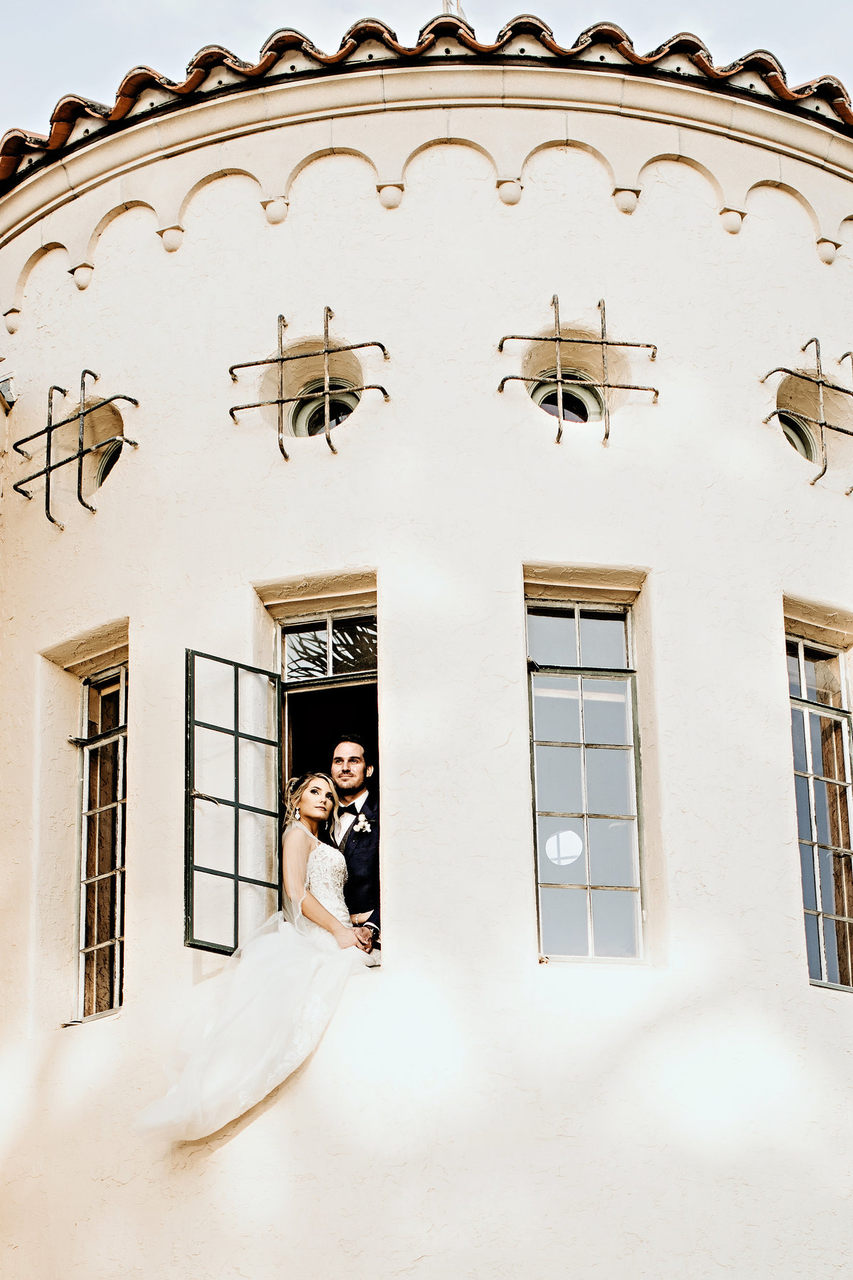A picture from outside at a distance of a bridal couple standing close together in an opened window in a picturesque tower at their wedding venue