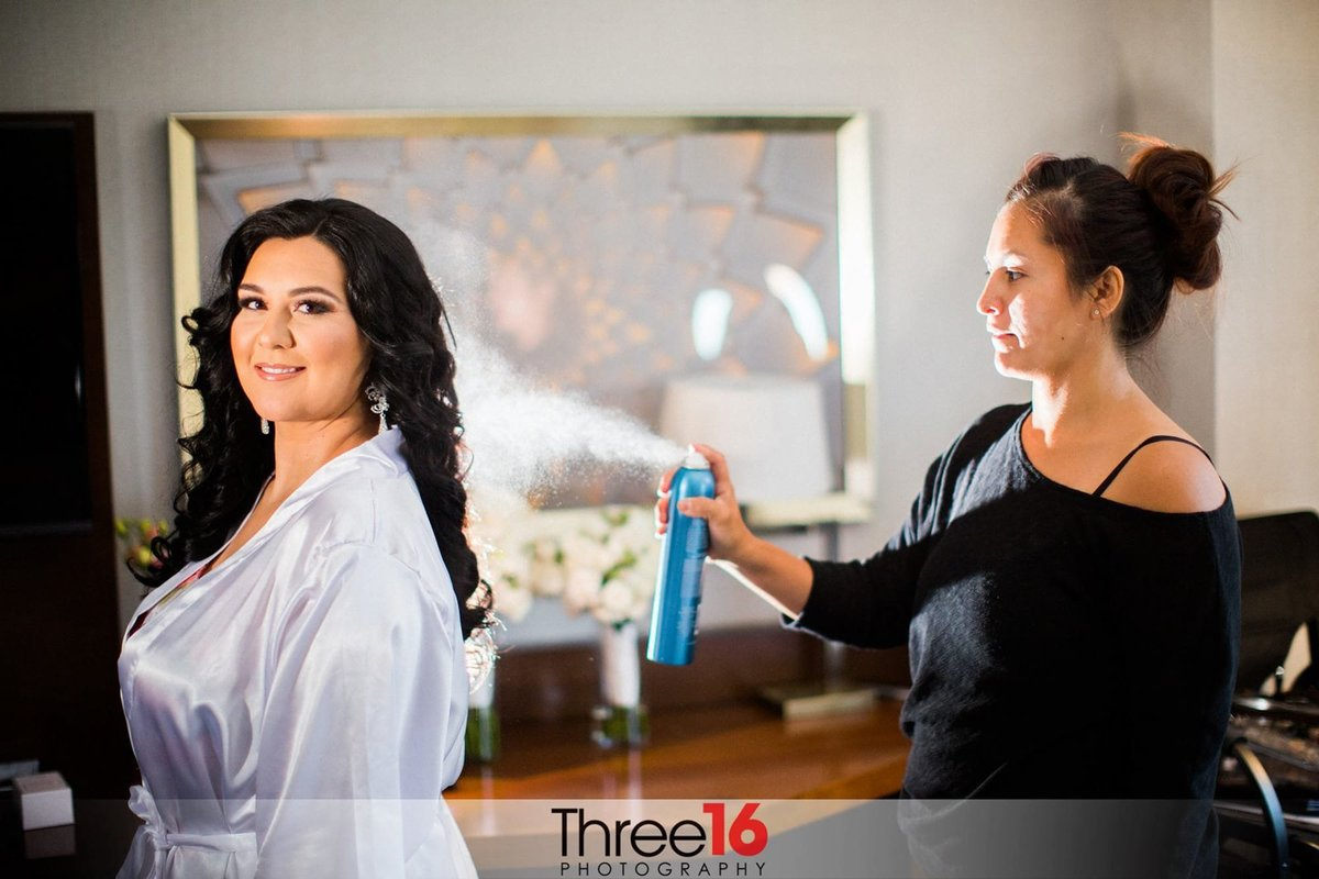 Bride having her hair sprayed while getting dressed for her wedding ceremony