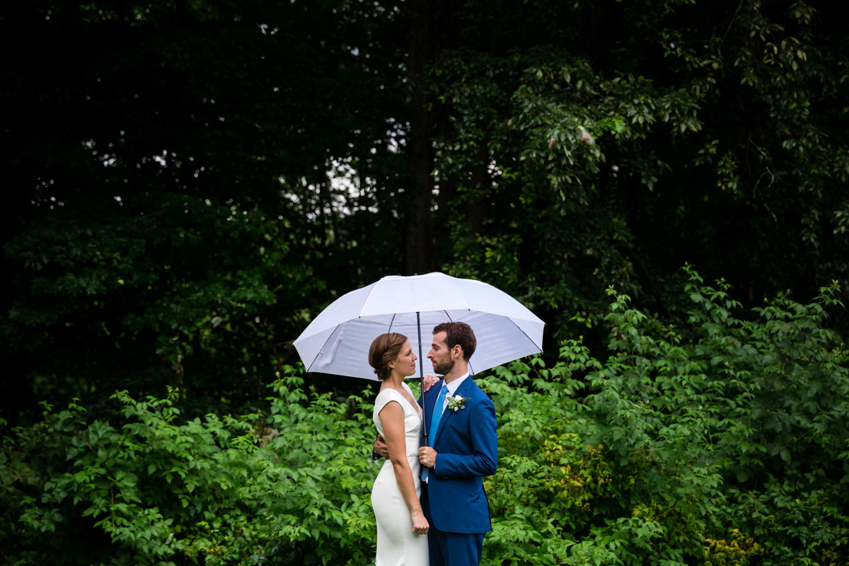 The bride and groom hold each other close in the rain under an umbrella at Common Man Italian Greenhouse in PLymouth NH