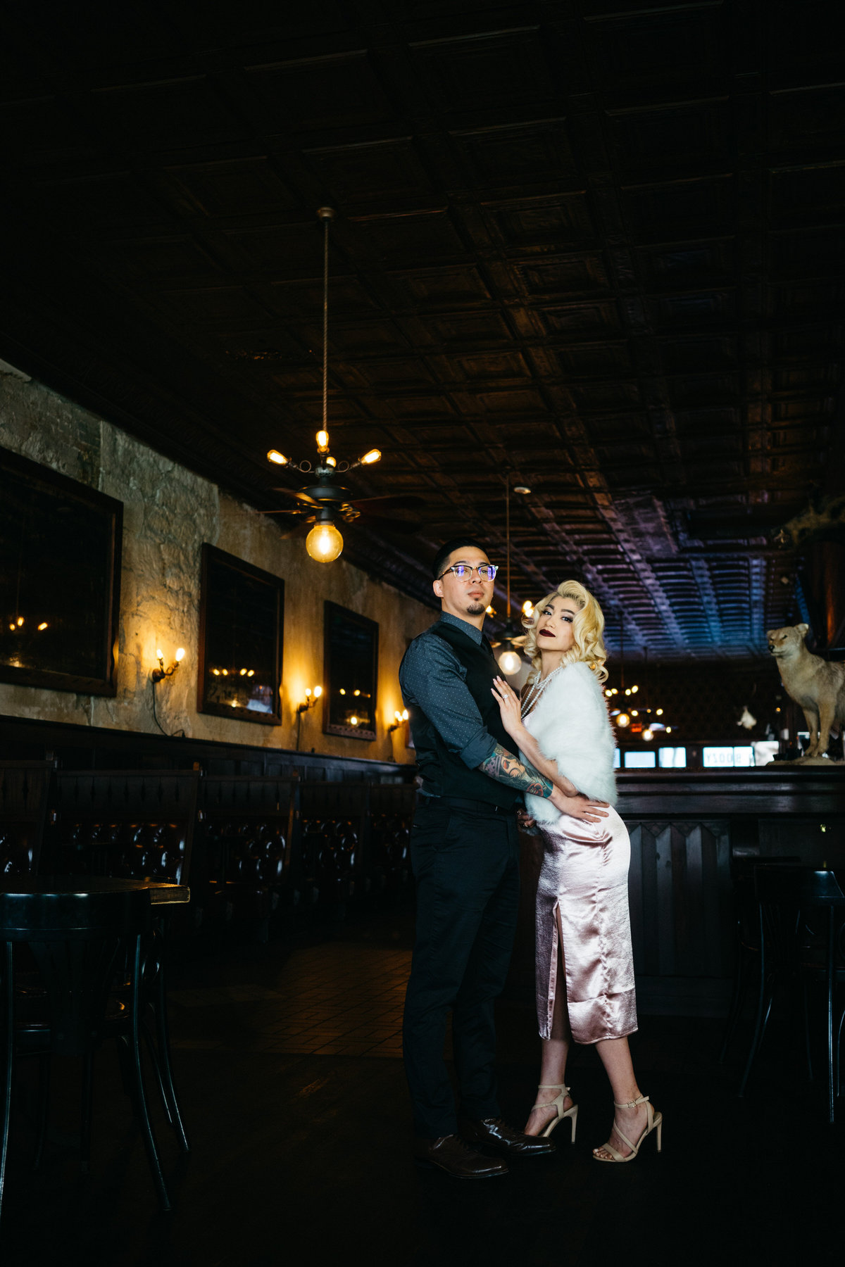 Couple posing for a picture for their engagement session at a bar in downtown San Antonio.