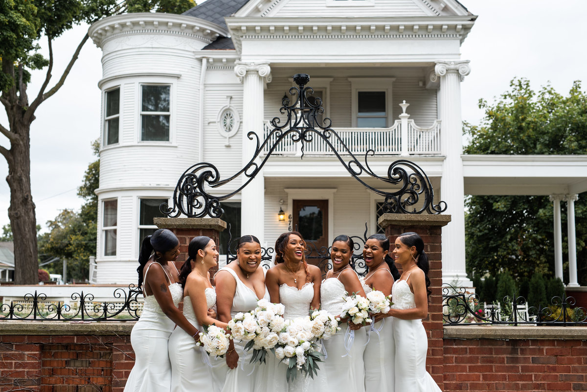 Bride and her bridesmaids all in white dresses standing in front of a mansion laughing.