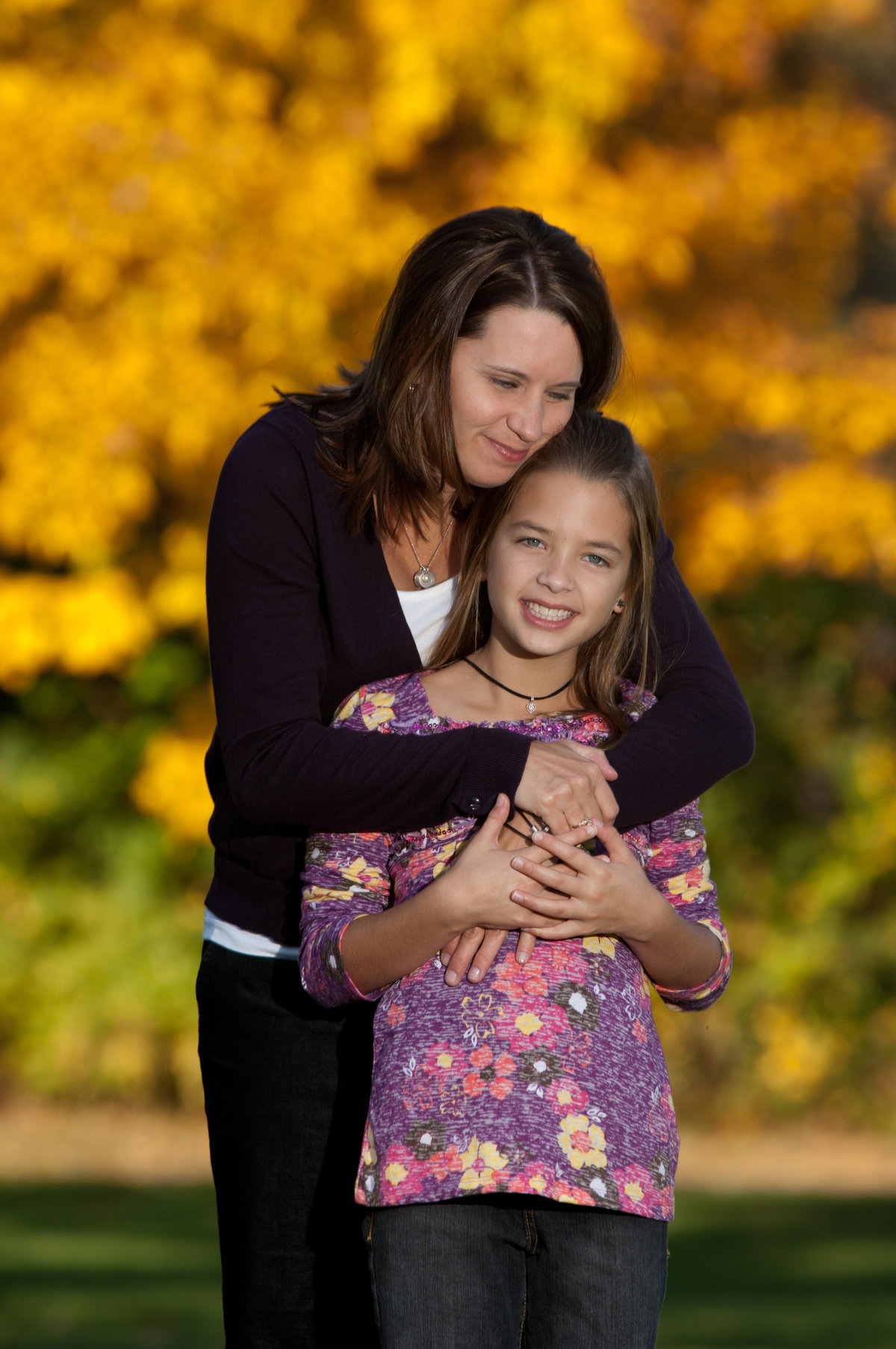 Mom hugging her daughter during a fall family portrait