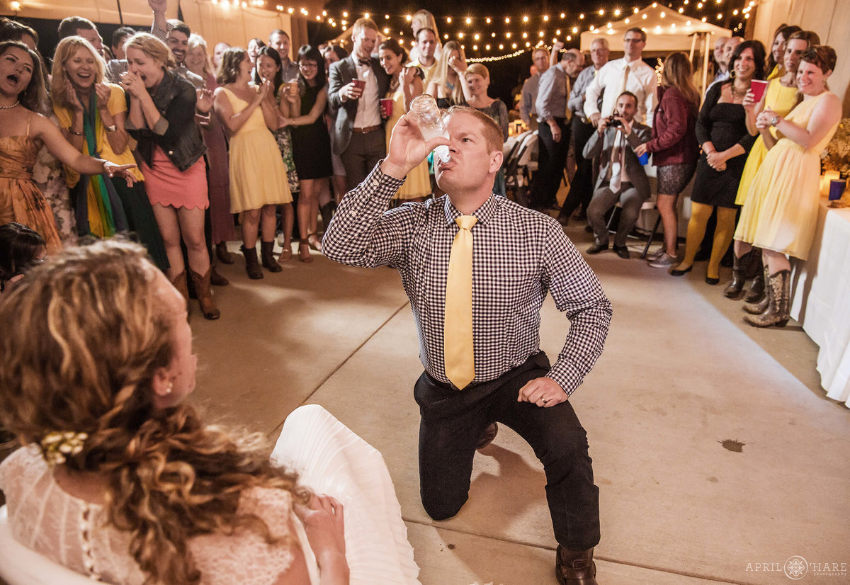 Groom is smirnoff iced by his bride during garter toss at Estes park YMCA of the Rockies wedding in Colorado