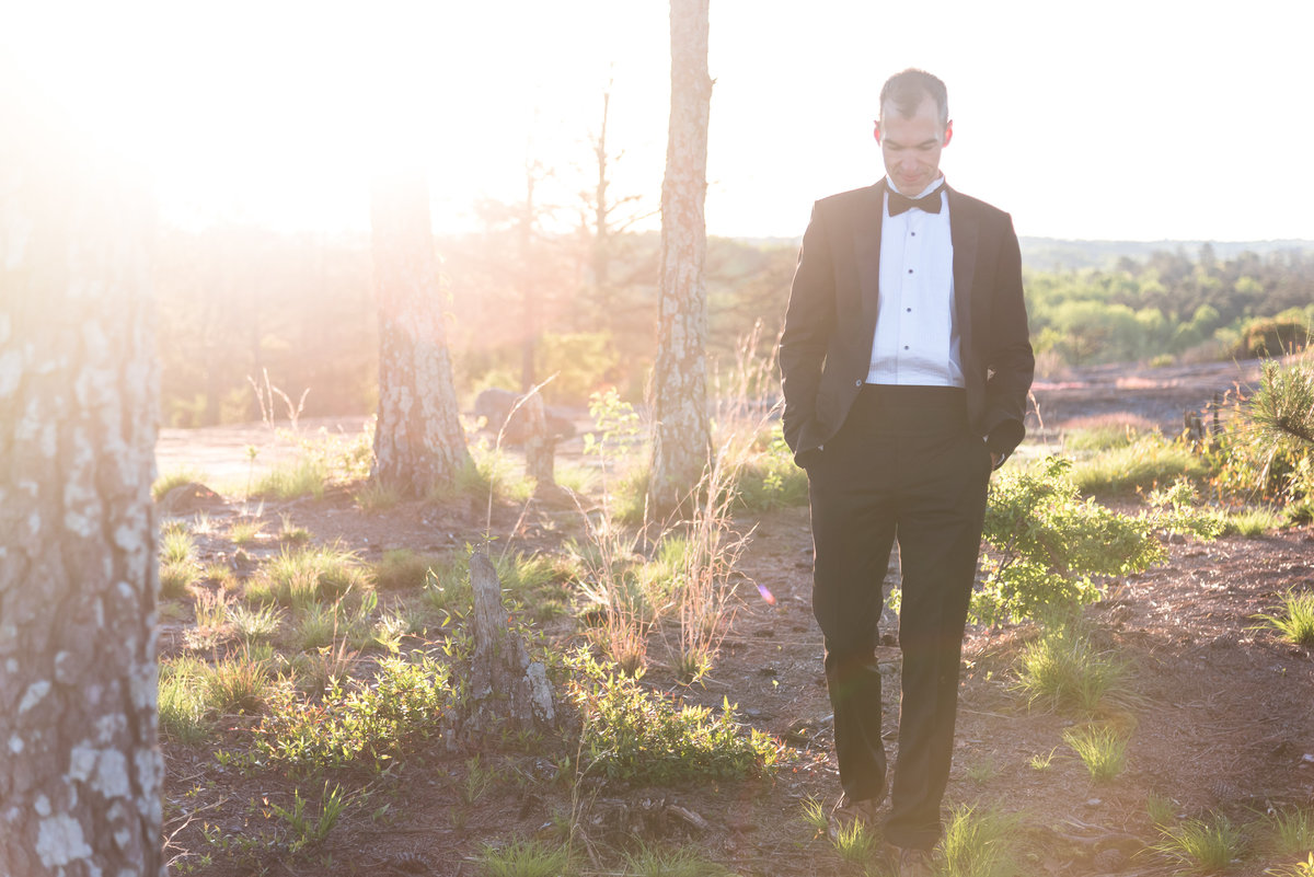 Jonathan walks on a mountain at sunrise in a tuxedo