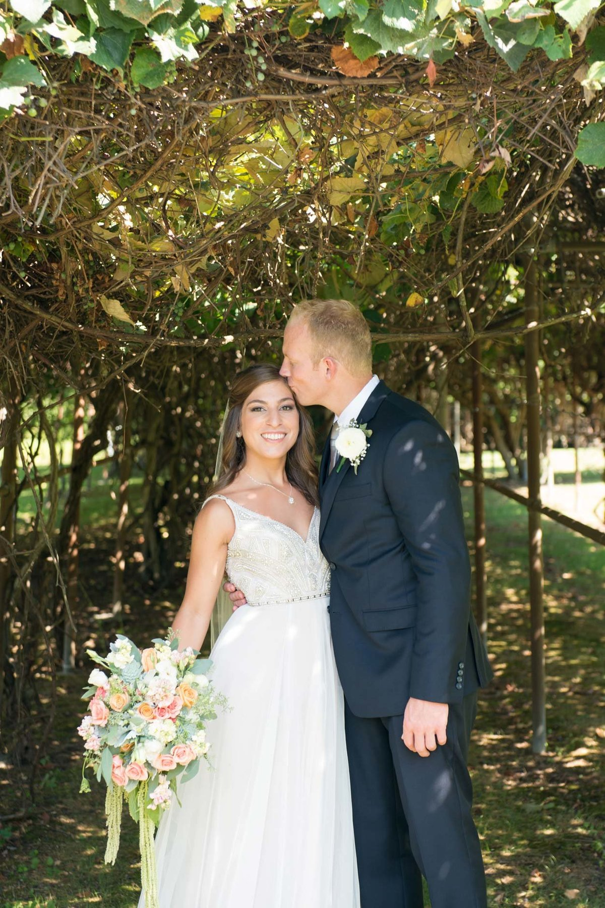Bride and groom outside in trail under flowers with groom kissing bride at Flowerfield