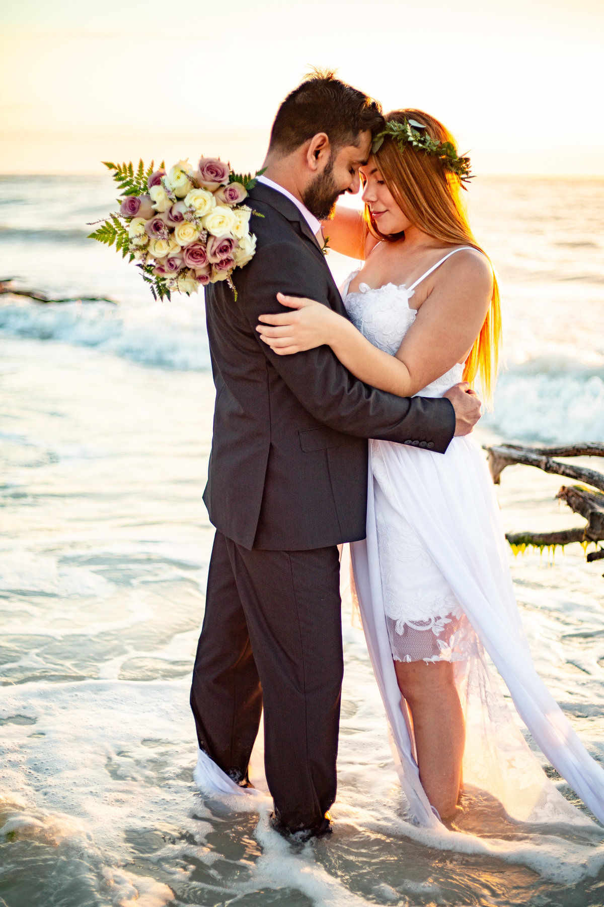 Bride and groom in ocean at the beach in Clearwater, Florida as they share an intimate moment at sunset on their wedding day with her wedding gown flowing in the ocean and she holds her cream, green, and purple bouquet around her groom's back