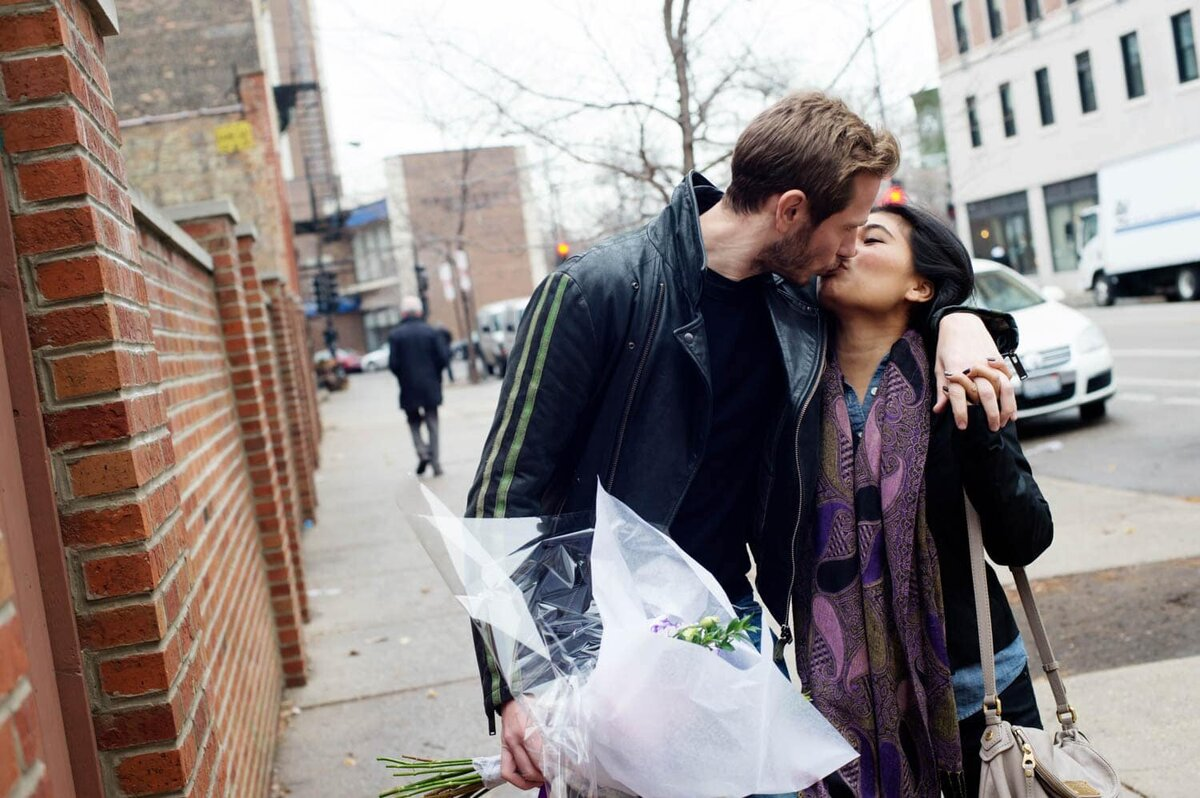 a man and woman kiss in the street while walking during their engagement photos
