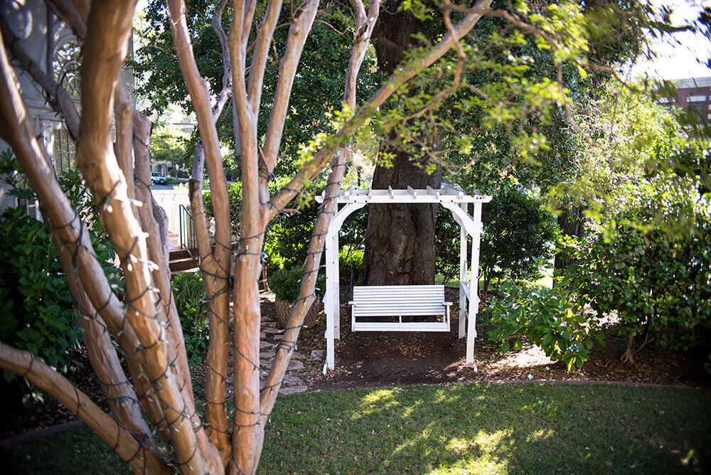 Tucked away under an oak tree, this swinging bench is a perfect hidden spot for a first look or a private moment.