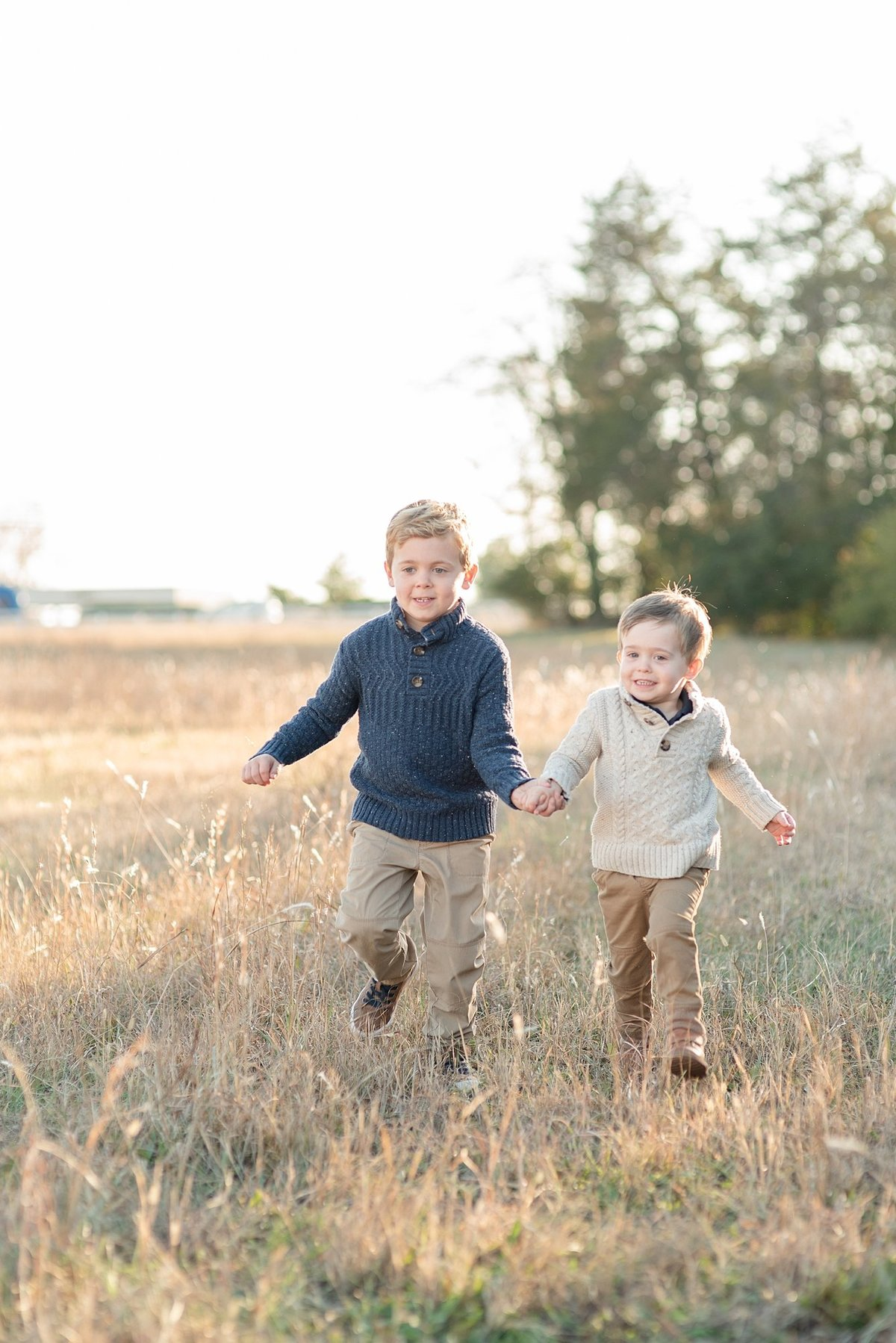 Two brothers are holding hands and running through a field in Nashville Tennessee