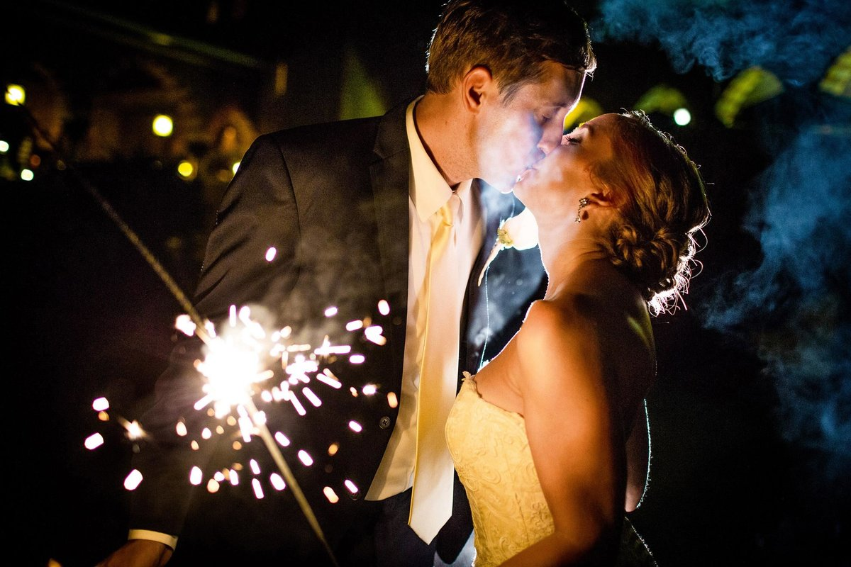 A couple kisses while holding a sparkler at their Medinah Country Club wedding.