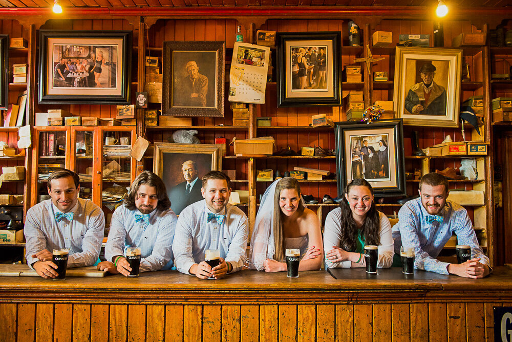 Bride with groom and groomsmen in traditional Irish pub in Dingle wearing baby blue bow ties and drinking Guinness