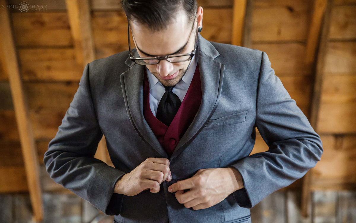 Groom buttons his suit jacket before wedding ceremony at The Barn at Evergreen Memorial Park in Colorado