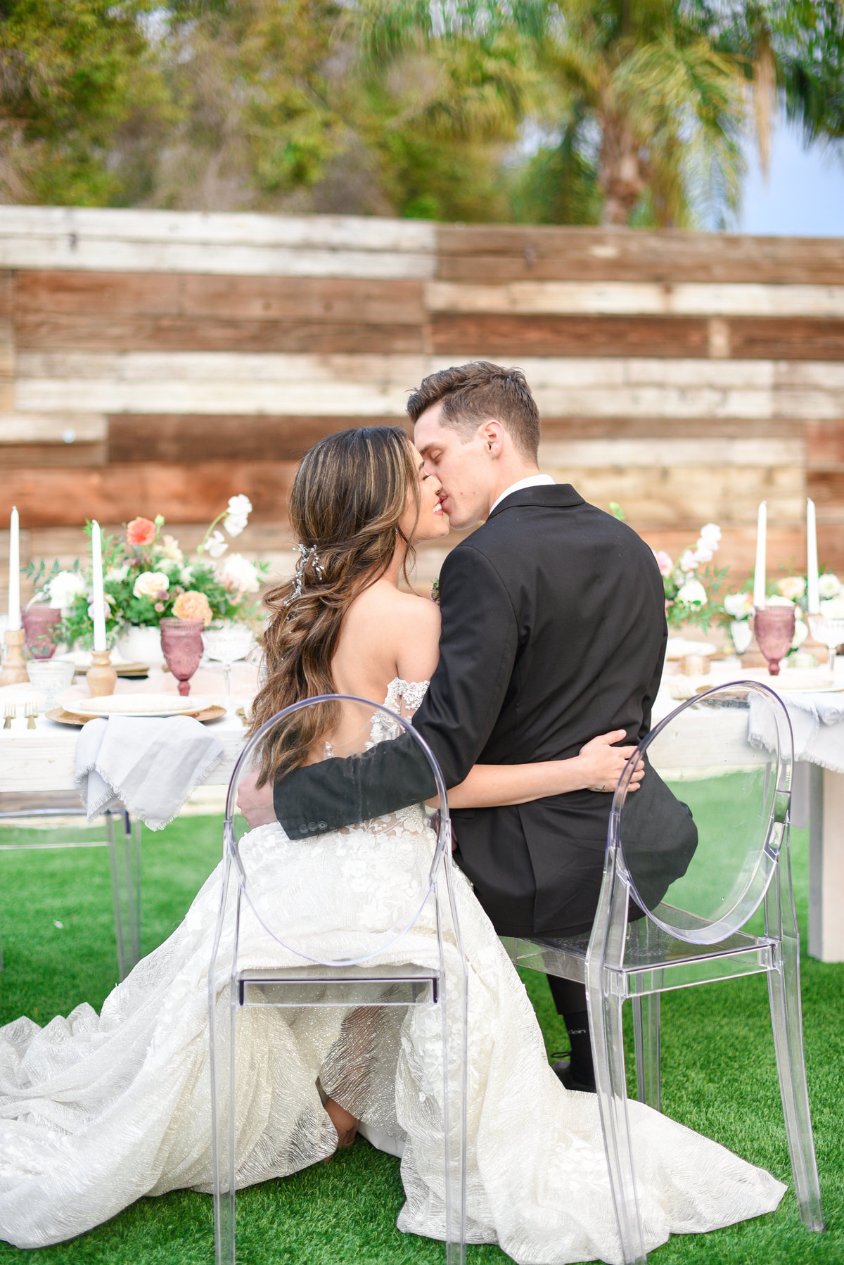 bride and groom kiss while sitting on ghost chairs