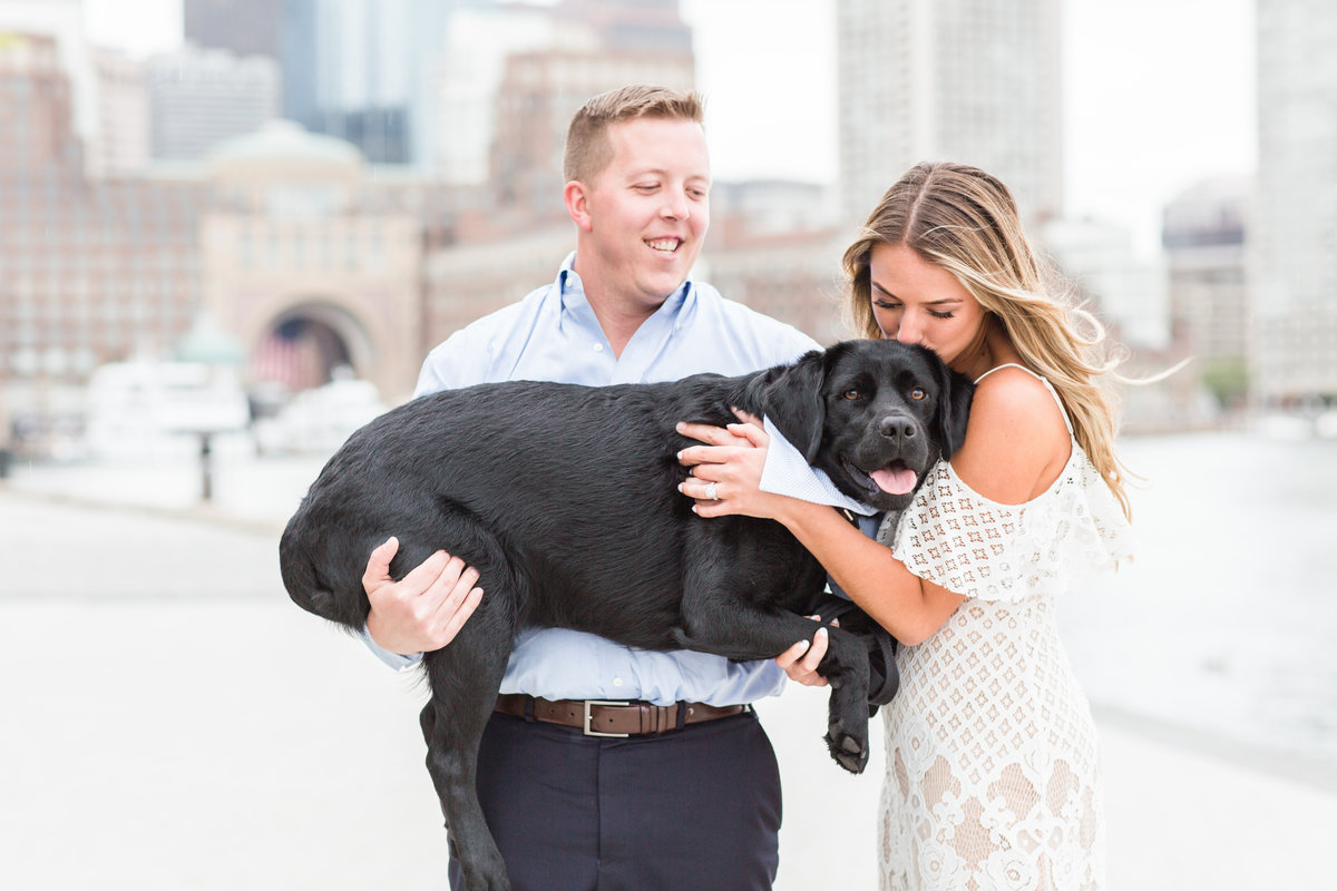Couple kissing their black lab in the Boston Seaport