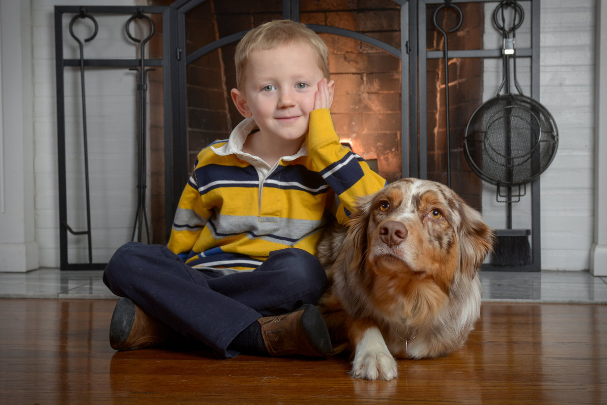 A boy and his dog in front of a fireplace during a family portrait session