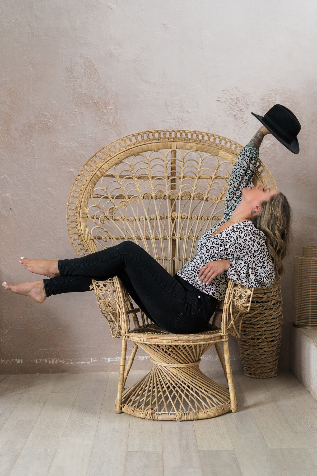 business women posing on a chair holding a hat