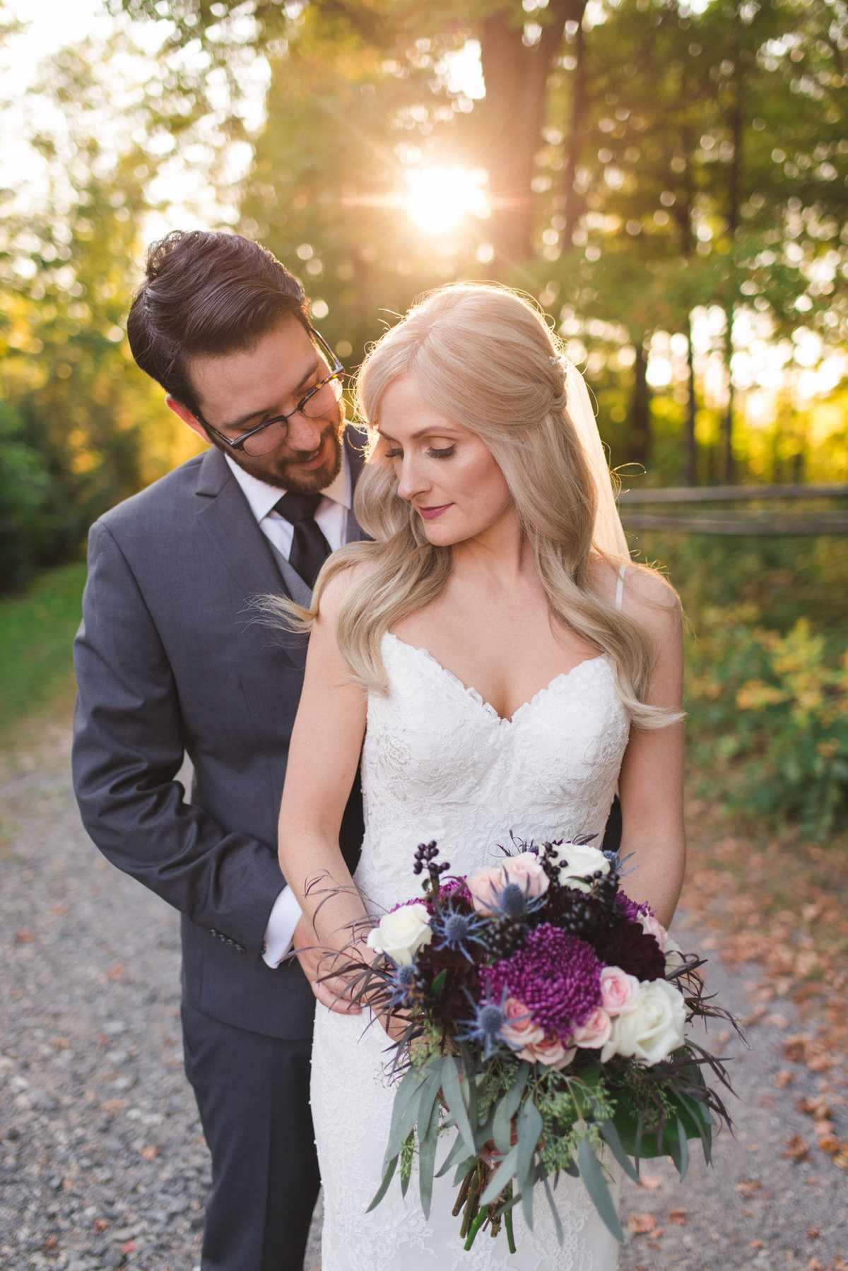 couple standing together at sunset with beautiful floral bouquet