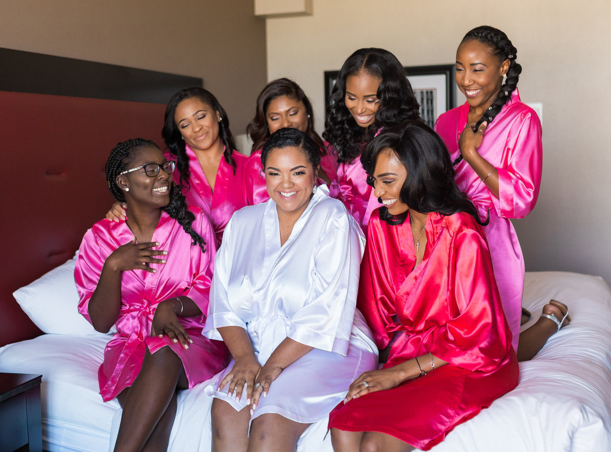 Bridesmaids in pink and white robes at wedding