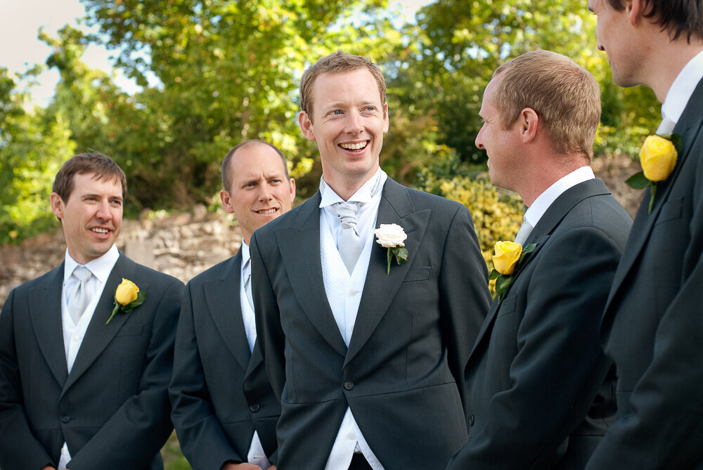Red haired groom wearing a light grey cravat and dark grey tailcoat with white buttonhole laughing with his groomsmen