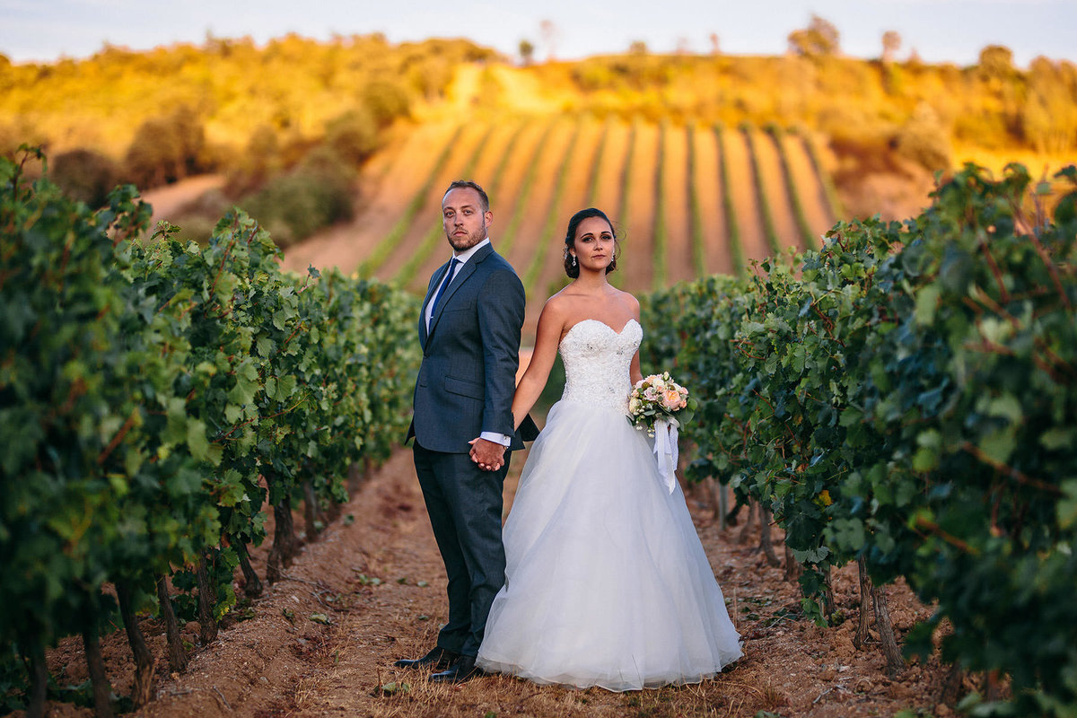 Bride & groom posing in front of vineyards after their Nice, France wedding.