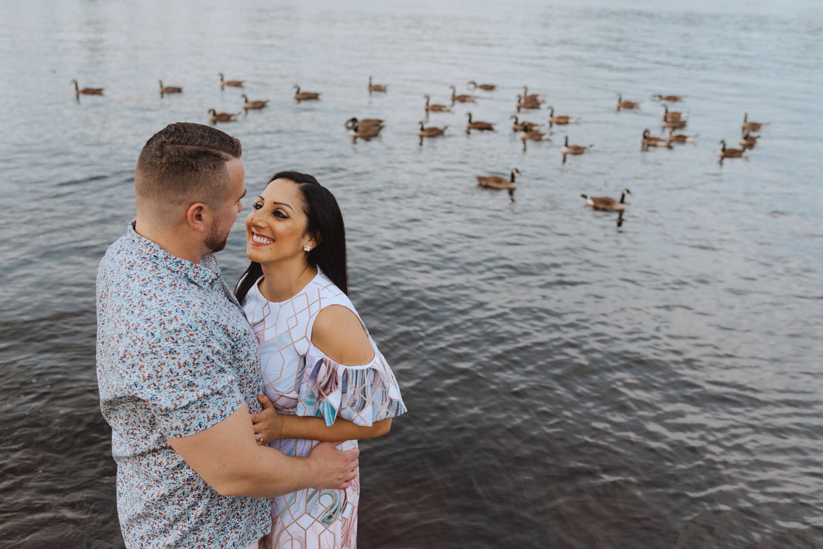 engaged couple standing by the water with canada geese in the water