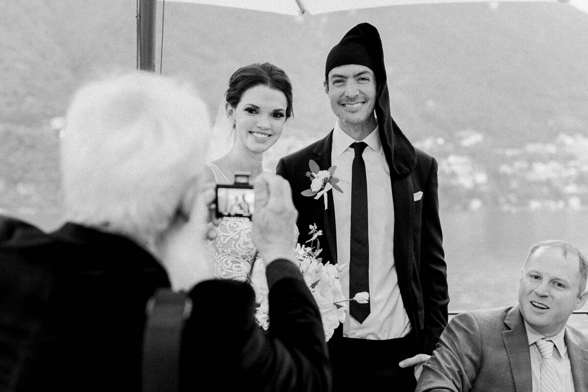 man taking photograph of bride and groom at Italian wedding reception black and white