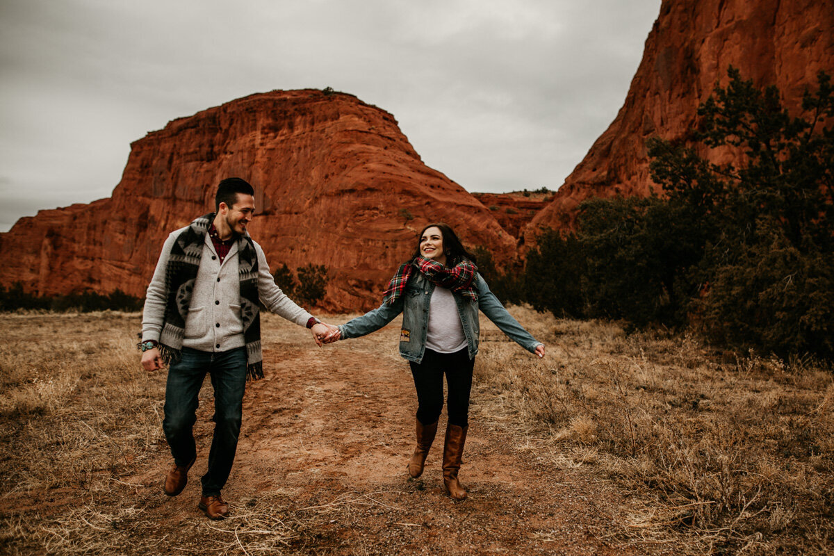 engaged couple running in front of a red rock mountain