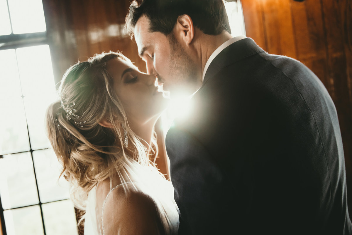 A photograph of a closeup view of a bridal couple nearly kissing in a romantic moment as the sunlight peeks in from behind them through a window